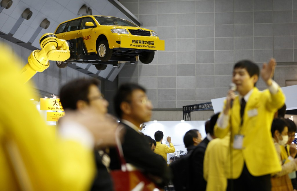 A Fanuc Corp. employee speaks to attendees as an industrial robots moves a vehicle during a demonstration at the International Robot Exhibition 2015 in Tokyo, Japan, on Tuesday, Dec. 2, 2015. Photographer: Tomohiro Ohsumi/Bloomberg